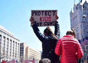 """girl on someone's shoulders at a rally with a sign that says """"protect kids not guns"""""""